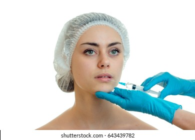 Portrait of a young girl in a medical CAP which the doctor injects the vaccine on the face with gloved hands