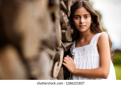 Portrait of young girl next to stack of firewood.