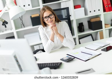 Portrait of a young girl in the office at the table.