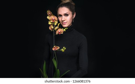 Portrait of young girl with orchid on black background
