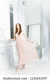 Portrait of a young girl in a pink dress in a bright room