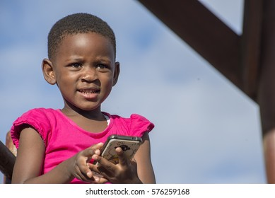 Portrait of a young girl in a pink dress against a blue sky with a mobile phone in her hands.