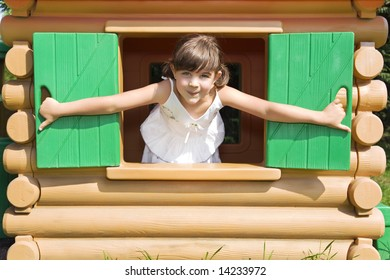 Portrait of young girl in play house outdoors.