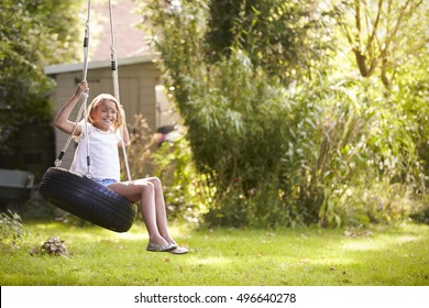 Portrait Of Young Girl Playing On Tire Swing In Garden