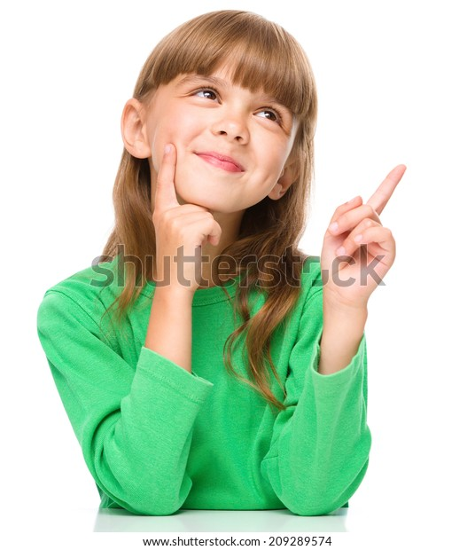 Portrait of a young girl pointing up using index finger, isolated over white