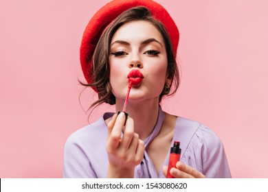 Portrait of young girl in red beret painting her lips with bright lipstick on pink background