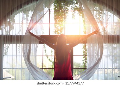 Portrait of a young girl in a red dress and a yellow hat while she is opening a curtain the let the light come through the window.