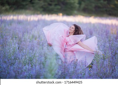portrait of young girl in sage  field wearing light pink dress looking like peony flower background
