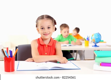 Portrait of a young girl in school at the desk.