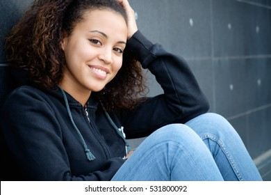Portrait of young girl seated in urban place