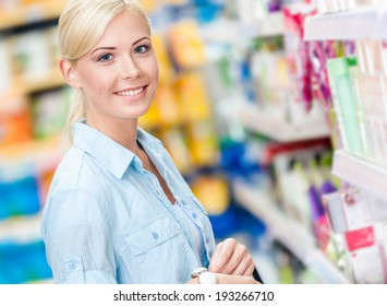 Portrait of young girl at the shop standing near the shelves with cosmetics