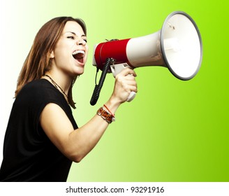 portrait of a young girl shouting with a megaphone over a green background
