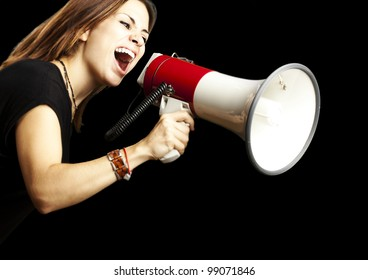 portrait of young girl shouting with megaphone over black background