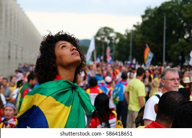 Portrait of a young girl shrouded in the flag of Brazil. In the background a lot of people. World Youth Day  Poland 2016