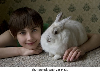 Portrait of a young girl  sitting at table holding  bunny