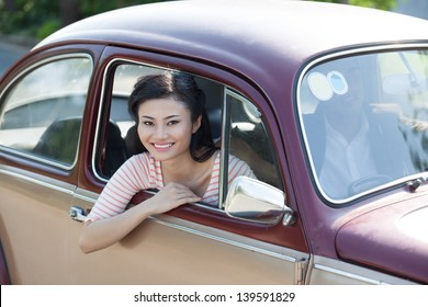 Portrait of a young girl sitting in a vintage car and smiling