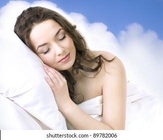 Portrait of a young girl sleeping on a clouds