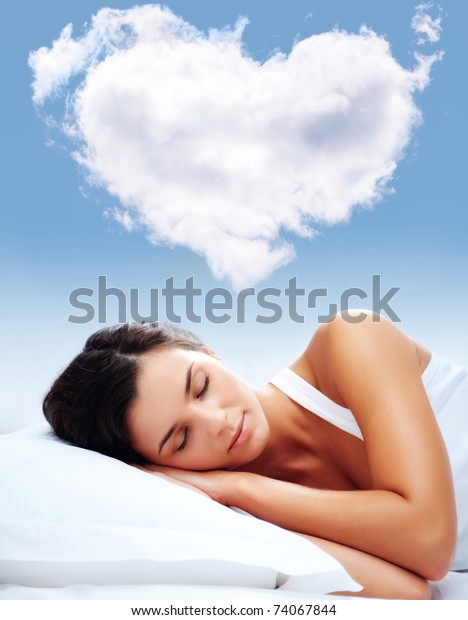Portrait of a young girl sleeping on a pillow with heartshaped cloud over her