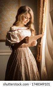 Portrait of a young girl standing near the window and smiling reading a letter. Historical reconstruction - Shutterstock ID 1748349101