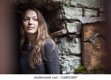portrait of a young girl at the stone wall