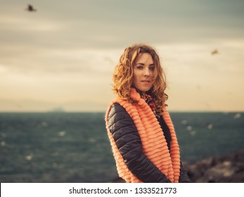 Portrait of the young girl with the stormy sea and clouds behind her