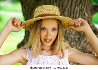 Portrait of a young girl in a straw hat