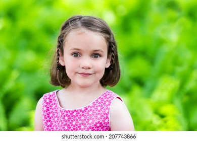 A portrait of a young girl in a summer dress smiling outside in a outdoor park-like setting.