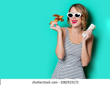 portrait of a young girl in sunglasses with money and wooden airplane on green background