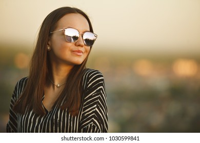 portrait of a young girl in sunglasses with reflective glasses.