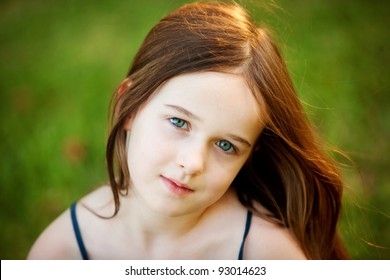 A portrait of a young girl taken outdoors.  She is beautiful and relaxed and is making eye contact with the camera.