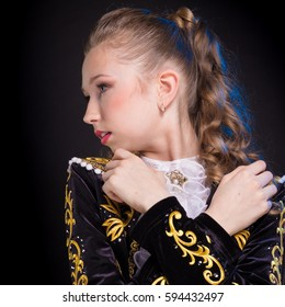 portrait of a young girl teenager in a black bullfighter suit dancing on a dark background in the studio