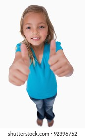 Portrait of a young girl with the thumbs up against a white background