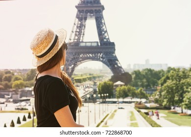 Portrait of young girl traveler at straw hat near famous Eiffel tower on beautiful day