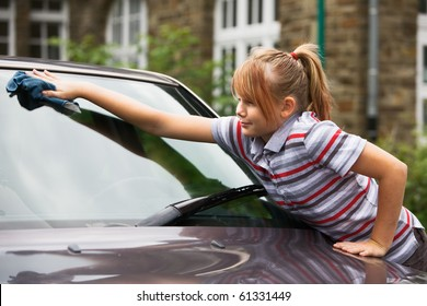 Portrait of young girl washing car