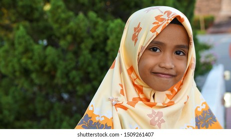 "Portrait of young girl wearing hijab and malay traditional cloth ""baju kurung""."
