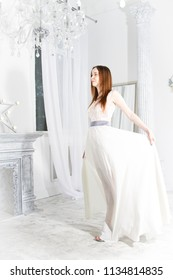 Portrait of a young girl in a white dress in a bright room with columns