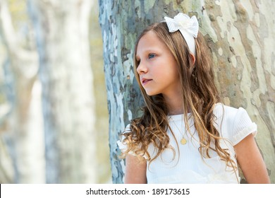 Portrait of young girl in white dress standing next to tree.