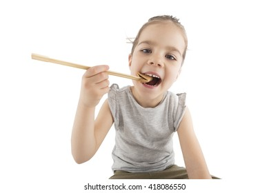 Portrait of young girl who is  eating  Asian cookies with a chopsticks, isolated on white.
