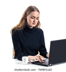 Portrait of young girl (woman) sitting in front of laptop and typing on keyboard. Isolated on white background. Cup of tea/coffe