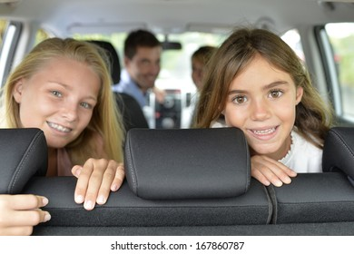 Portrait of young girls in car ready for car trip
