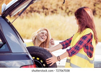Portrait of a young girls having some car trouble on a sunny day.