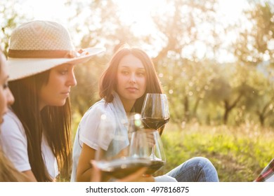Portrait of young girls holding glasses of red wine and spending time together in the garden