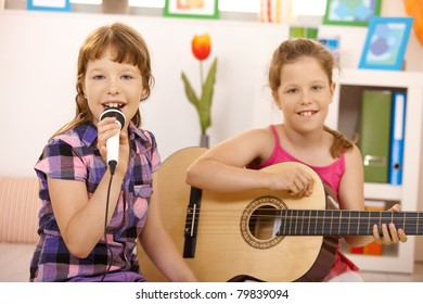 Portrait of young girls performing music, singing and playing guitar, smiling at camera.?