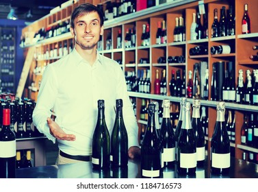 portrait of young glad male customer taking bottle of wine in store