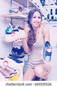Portrait of young glad smiling cheerful woman looking confused with two pair of shoes in fashion department