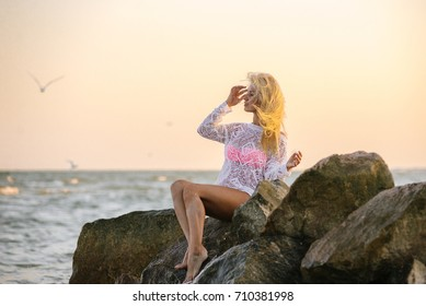 Portrait of young glam smiling blond lady in pink swimming bra standing on beach seaside looking aside. Her hair blown by the wind.