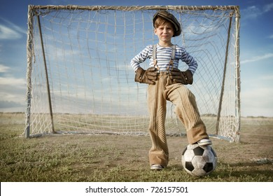 Portrait of a young goalkeeper with a ball at the gate