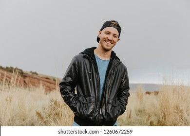 Portrait of Young Good Looking Handsome Man Smiling with Backwards Hat in Leather Jacket Outside in Isolated Rural Field of Tall Grass in the Meadow Nature Outside Autumn Season