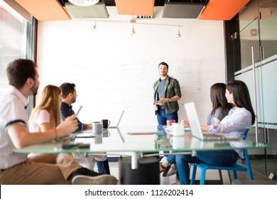 Portrait of a young good looking man giving a business presentation to his colleagues in meeting room