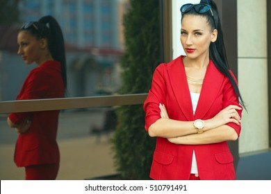 Portrait of young gorgeous dark-haired businesswoman in classic red suit and golden watch with sunglasses on her head standing at office building with mirrored windows. Outdoor shot. Copy-space